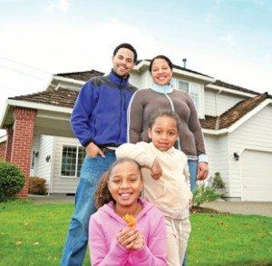 Una sonrisa de la familia de cuatro, de pie en el césped verde de una gran casa suburbana.