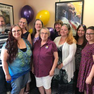 Nueve miembros de SEIU posan sonriendo con globos morados y dorados.