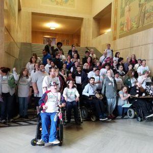"""Docenas de personas se hacen pasar por un grupo en los escalones dentro del edificio del Capitolio del Estado de Oregon. Muchos llevan camisetas que dicen """"Oregon Careworks"""""""
