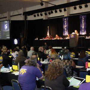 Los líderes miembros de SEIU se sientan en mesas largas, escuchando un discurso en el Concilio General.