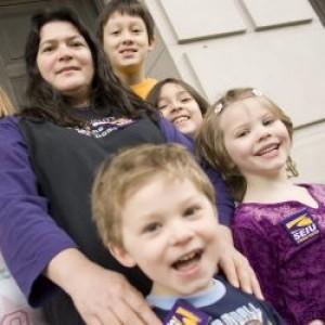 Un trabajador de cuidado infantil está rodeado por seis niños sonrientes.