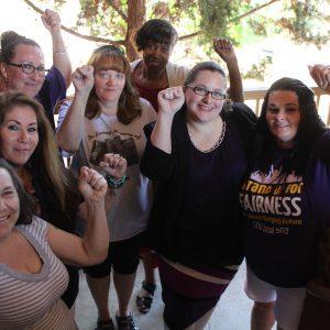 Un grupo de 5 miembros de SEIU sostienen sus puños en el aire sonriendo en un grupo cerrado.