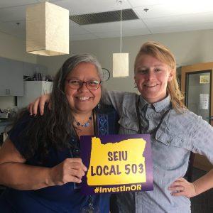 """Dos personas están parados sonriendo ampliamente. Uno sostiene un cartel con el contorno del estado de Oregon y dice """"SEIU LOCAL 503 #InvestInOR"""""""