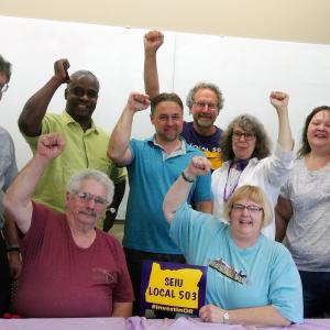 Un grupo de trabajadores de Educación Superior de SEIU sonriendo en una sala de reuniones, con los puños levantados en el aire.
