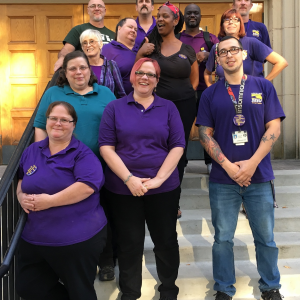 Un grupo de 12 miembros de SEIU PPS está sonriendo en los escalones de la sala del sindicato.