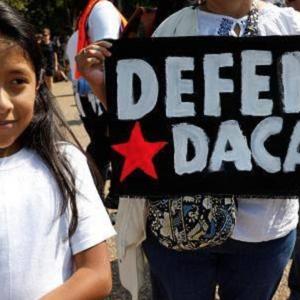 """Un niño pequeño está sonriendo junto a un cartel que sostiene un adulto. El letrero dice """"DEFENDER DACA"""""""