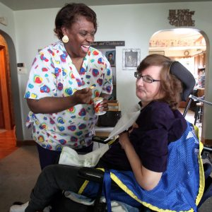 Un cuidador de cuidados domiciliarios en bata se ríe mientras ayuda a un cliente a comer yogur.