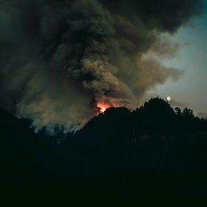 Un incendio forestal en la cima de una colina por la noche.