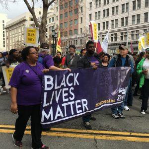 """Cuatro manifestantes en una protesta más grande llevan un cartel que dice """"Black Lives Matter"""" con el logo de SEIU."""