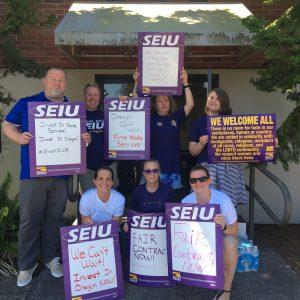 """Un grupo de miembros de SEIU se ponen de pie y se arrodillan sosteniendo carteles, algunos de los cuales dicen: """"IN chaleco en los servicios estatales"""", """"¡No podemos esperar! ¡Invierta en Oregon ahora!"""""""