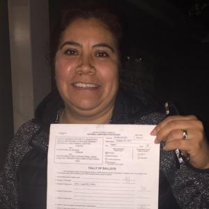 Una persona sonriente sostiene un recuento de votos en una hoja de papel en blanco.