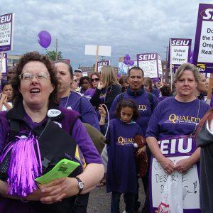 Una multitud de miembros de SEIU se para en un mitin.