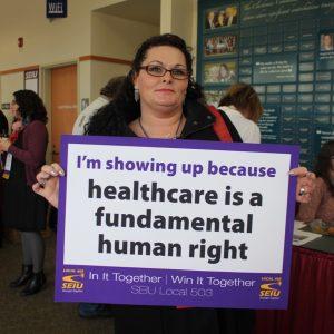 """Un miembro de SEIU sostiene un letrero que dice """"Me voy a presentar porque la atención médica es un derecho humano fundamental""""."""