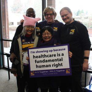 """Cinco miembros de SEIU que visten ropa de SEIU se agrupan, sonriendo, alrededor de un letrero que dice """"Me voy porque la atención médica es un derecho humano fundamental""""."""
