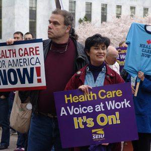 """Dos personas sostienen carteles en un mitin sindical. Los carteles decían """"Atención médica para Estados Unidos ahora"""" y """"Atención médica: una voz en el trabajo. ¡Ya está!"""""""
