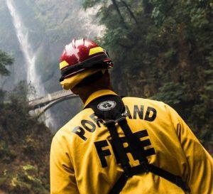 Спина портлендского пожарного в желто-красной защитной экипировке перед водопадом Мултома.