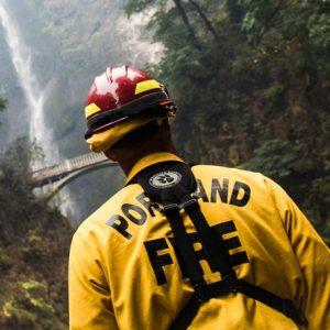 La parte de atrás de un bombero de Portland con equipo de seguridad amarillo y rojo, frente a Multhomah Falls.