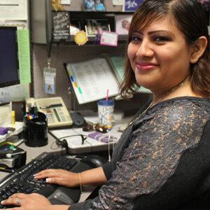 Una mujer sonriendo en un escritorio en un cubículo de trabajador estatal