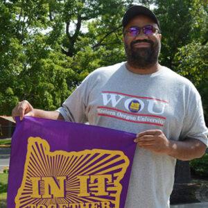 Un miembro afroamericano de SEIU con una camiseta de WOU con una bandera morada que dice 'In It Together'