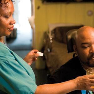 Una mujer vistiendo uniformes médicos ayudando a un hombre a beber con una pajita. El hombre está sentado en una silla de ruedas y viste una camiseta ADAPT