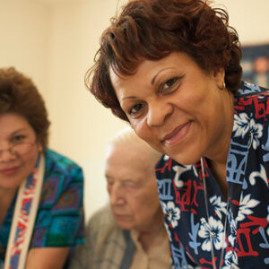 Two women in scrubs leaning over a table in a nursing home and smiling. An elderly man sits in the background