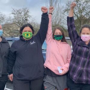Năm phụ nữ trẻ đeo khẩu trang bằng vải che mặt đứng cùng nhau giơ cao nắm đấm